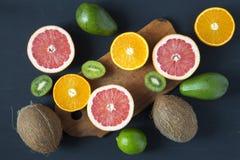 平的位置 顶视图 切的五颜六色的新鲜水果:猕猴桃、桔子、葡萄柚和普通话在木板 椰子、石灰和avoca 库存图片