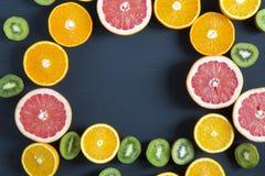 平的位置 顶视图 切的五颜六色的新鲜水果:猕猴桃、桔子、葡萄柚和普通话在黑背景 库存图片