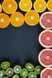 平的位置 顶视图 切的五颜六色的新鲜水果:猕猴桃、桔子、葡萄柚和普通话在黑背景 免版税库存照片