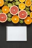 平的位置 顶视图 笔记本用切的五颜六色的新鲜水果:猕猴桃、桔子、葡萄柚和普通话在黑背景 库存图片
