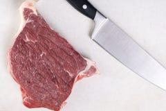 平的在未加工的牛排witk厨房厨师刀子上的位置顶上的视图在白色大理石背景桌上 免版税图库摄影