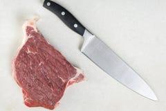 平的在未加工的牛排witk厨房厨师刀子上的位置顶上的视图在白色大理石背景桌上 库存照片