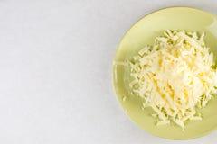 平的在板材的位置上面搓碎干酪有在白色大理石上的拷贝空间的 免版税库存照片