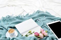 平的在白色毯子的位置片剂、电话、咖啡和花有绿松石格子花呢披肩的 免版税库存图片