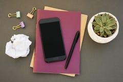 平的有桃红色笔记本的,智能手机,多汁植物位置现代最小的工作区书桌 女性书桌 库存照片