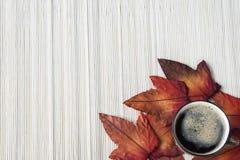 平的被放置的咖啡与秋叶的反对竹背景 免版税库存图片