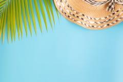 平的被放置的照片椰子叶子和帽子在蓝色背景、顶视图和拷贝空间蒙太奇的您的产品 免版税库存图片