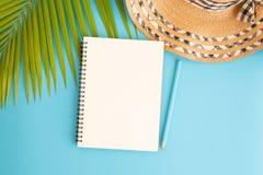 平的被放置的照片空白笔记本和椰子叶子和帽子在蓝色背景、顶视图和拷贝空间蒙太奇的您的产品 免版税库存照片