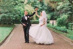 水平的观点的跳舞新婚佳偶在绿色公园 免版税库存图片