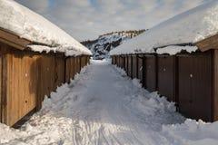 平行的棕色多个车库大厦、雪在地面上,山和白色云彩在蓝天 库存照片