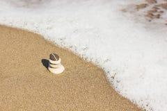 平衡了在美丽的几块禅宗石头海滩背景 免版税库存图片