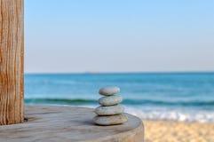 平衡了在被弄脏的美丽的几块禅宗石头海滩背景 免版税图库摄影