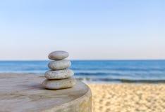 平衡了在被弄脏的美丽的几块禅宗石头海滩背景 免版税库存图片