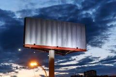 以平衡剧烈的天空为背景的空白的铁广告牌 库存照片