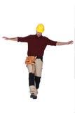 平衡在一条腿的建造者 免版税图库摄影
