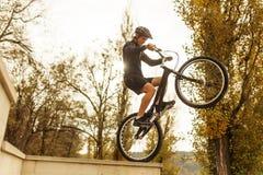平衡在一辆自行车的人在公园 免版税库存照片