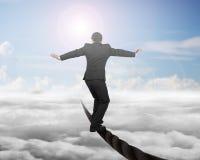 平衡在与天空潜水艇cloudscape的一根导线的商人 库存照片