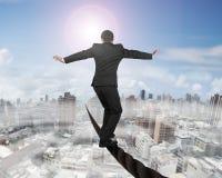 平衡在与太阳薄雾都市风景的一根导线的商人 免版税库存图片