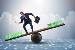 平衡在事业和家庭之间的商人在浓缩的事务 免版税库存图片