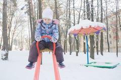 平衡在冬天操场跷跷板的小女孩 库存图片