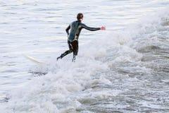 平衡在冲浪板的冲浪者在海波浪中间 免版税库存图片
