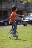 平衡在单轮脚踏车的男孩 免版税库存照片