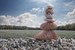 平衡在堆岩石的石头有农业地区背景 库存照片