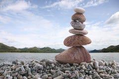 平衡在堆岩石的石头有河背景 免版税库存图片
