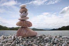平衡在堆岩石的石头有河背景 库存照片