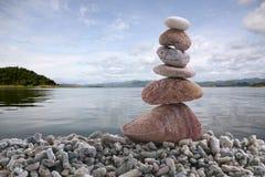 平衡在堆岩石的石头有河背景 图库摄影