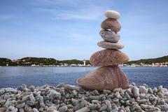 平衡在堆岩石的石头有海背景 库存照片