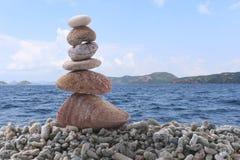 平衡在堆岩石的石头有海背景 免版税库存图片
