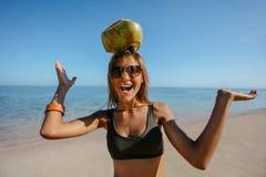 平衡在她的头的愉快的妇女一个椰子在海滩 库存图片