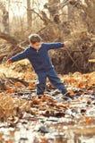 平衡在小河的岩石的男孩 免版税图库摄影