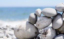 平衡在岩石海滩墙壁上的小平的岩石 库存照片