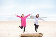 平衡在日志的两个青少年的女孩在海滩 免版税图库摄影