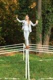 平衡在橄榄球小门的微笑的女孩 免版税库存照片