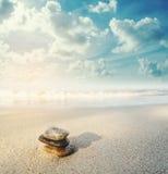 平衡在海滩的石头在日出,葡萄酒口气 图库摄影