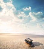 平衡在海滩的石头在日出,葡萄酒口气 免版税库存图片