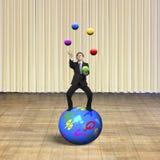 平衡在球形的商人玩杂耍与球 免版税库存照片