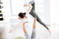 平衡在男性脚的妇女,当做acro瑜伽时 免版税图库摄影