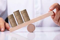 平衡在跷跷板的人的手被堆积的硬币 免版税图库摄影