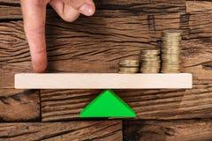 平衡在跷跷板的手指被堆积的硬币 免版税库存图片