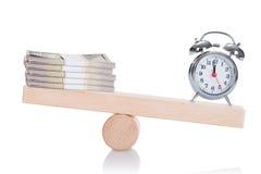 平衡在跷跷板的闹钟和美元捆绑 免版税库存图片