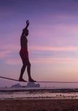 平衡在slackline的十几岁的女孩有在海滩的天空视图 免版税库存图片