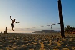 平衡在slackline的未认出的人在海滩 免版税库存图片