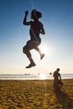 平衡在slackline的年轻人剪影在 免版税库存照片