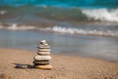 平衡小卵石堆积了一到一个在海海滩有蓝色波浪背景 免版税库存图片