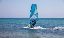 平衡小型客帆船的一个人 滑动在水上运动设备下的强的波浪 行动的风帆冲浪的热心者 Promoti 库存图片
