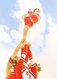 平衡往天空的年轻啦啦队员-啦啦队员合作 库存照片